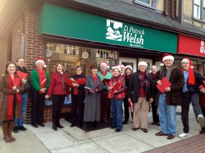 Carolers bring their cheer to D. Patrick Welsh on their trek through the village!  (See our own Linda H. in the red jacket?)