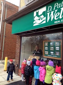 Little carolers from Trinity pre-school bring D. Patrick Welsh some holiday cheer as Becky Hansen looks on!