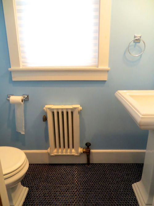 The powder room has a playful blue penny tile floor!